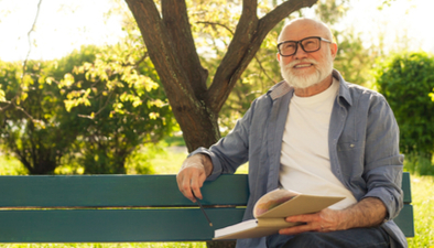 man reading on a park bench